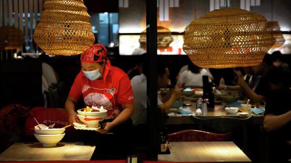Работник кафе убирает грязные тарелки в Пекине