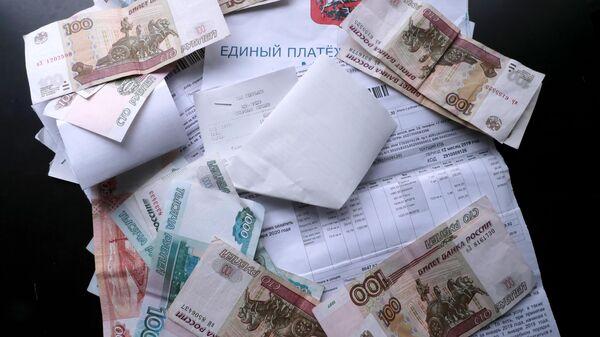 Денежные купюры и квитанции за оплату коммунальных услуг.