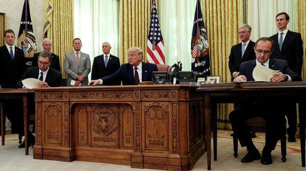 Президент Сербии Александр Вучич, президент США Дональд Трамп и премьер-министр Косово Авдулахом Хоти во время церемонии подписания соглашения об экономическом сотрудничестве