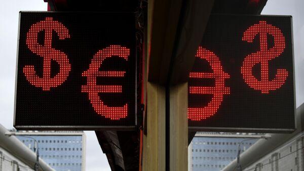 Электронное табло со знаками доллара и евро на одной из улиц в Москве