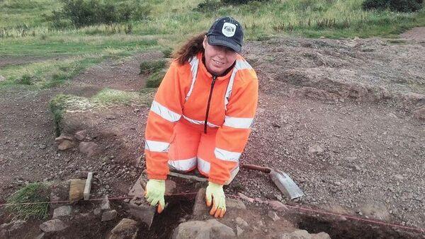 Археолог во время раскопок на горе Трон Артура в Шотландии