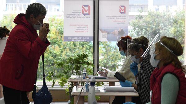 Женщина голосует на избирательном участке в Иркутске