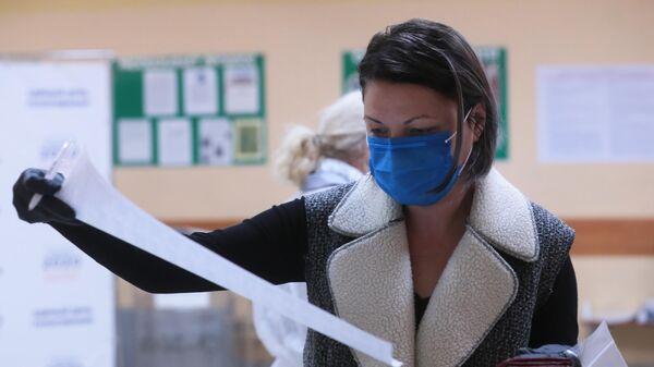Женщина голосует на дополнительных выборах в Совет депутатов муниципального округа Бабушкинского района Москвы