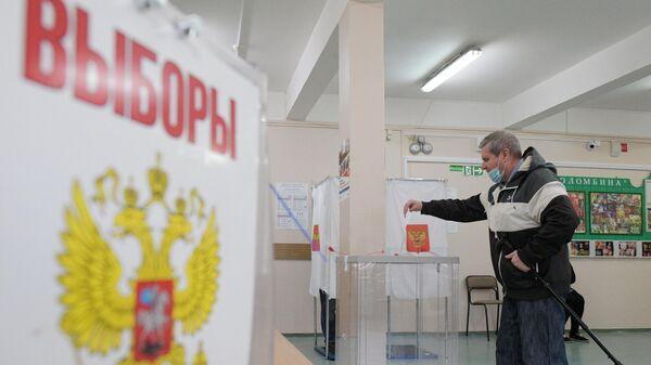 Мужчина опускает бюллетень в урну на избирательном участке