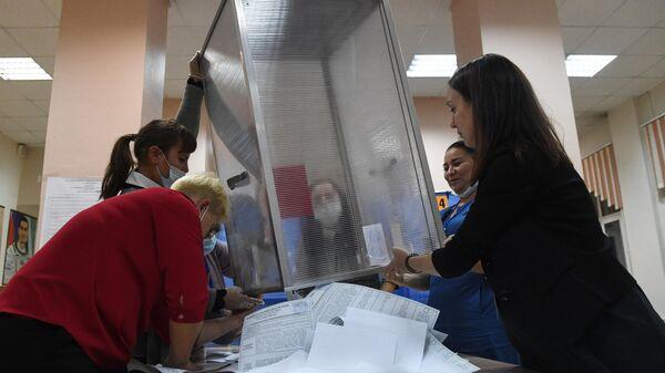 Выемка из урны для голосования заполненных избирательных бюллетеней на избирательном участке №645 в Иркутске