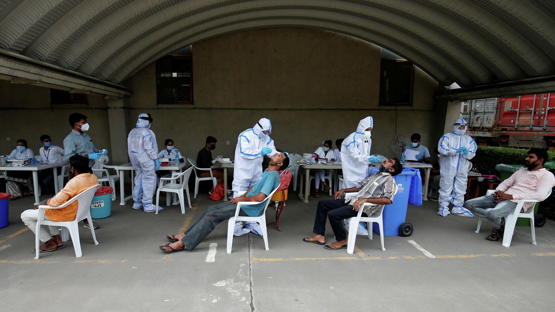 Медицинские работники берут мазки у рабочих мукомольного завода во время вспышки коронавирусной инфекции на окраине Ахмадабада, Индия - РИА Новости, 1920, 16.09.2020