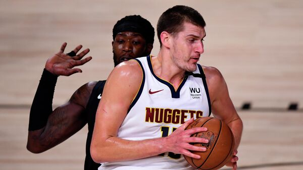 LAKE BUENA VISTA, FLORIDA - SEPTEMBER 15: Nikola Jokic #15 of the Denver Nuggets drives the ball against Montrezl Harrell #5 of the LA Clippers during the first quarter in Game Seven of the Western Conference Second Round during the 2020 NBA Playoffs at AdventHealth Arena at the ESPN Wide World Of Sports Complex on September 15, 2020 in Lake Buena Vista, Florida. NOTE TO USER: User expressly acknowledges and agrees that, by downloading and or using this photograph, User is consenting to the terms and conditions of the Getty Images License Agreement.   Douglas P. DeFelice/Getty Images/AFP