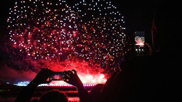 Люди фотографируют на мобильные телефоны салют на международном фестивале фейерверков Ростех, который проходит на территории парка Патриот.