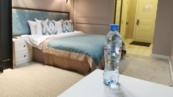 Бутылка воды на столике в номере 239 гостиницы Xander Hotel в Томске