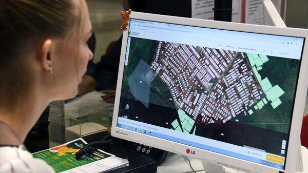Девушка выбирает участок земли по программе Дальневосточный гектар в Центре государственных и муниципальных услуг