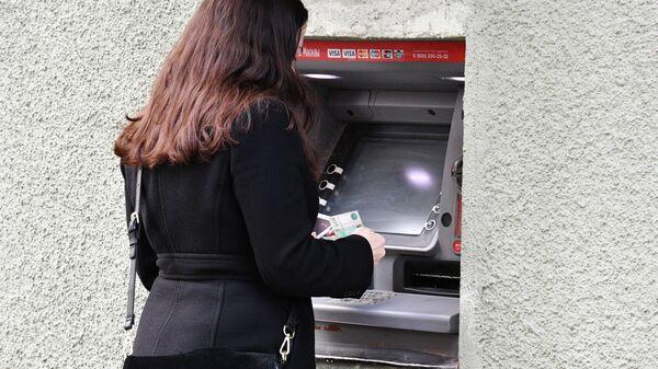 Девушка снимает наличные в банкомате на улице Москвы