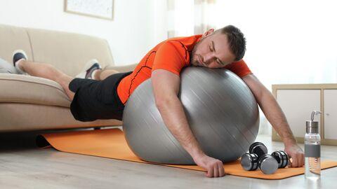 Ленивый человек со спортивным снаряжением дома