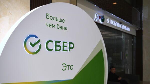 Новый логотип Сбербанка в холле отделения в Оружейном переулке в Москве