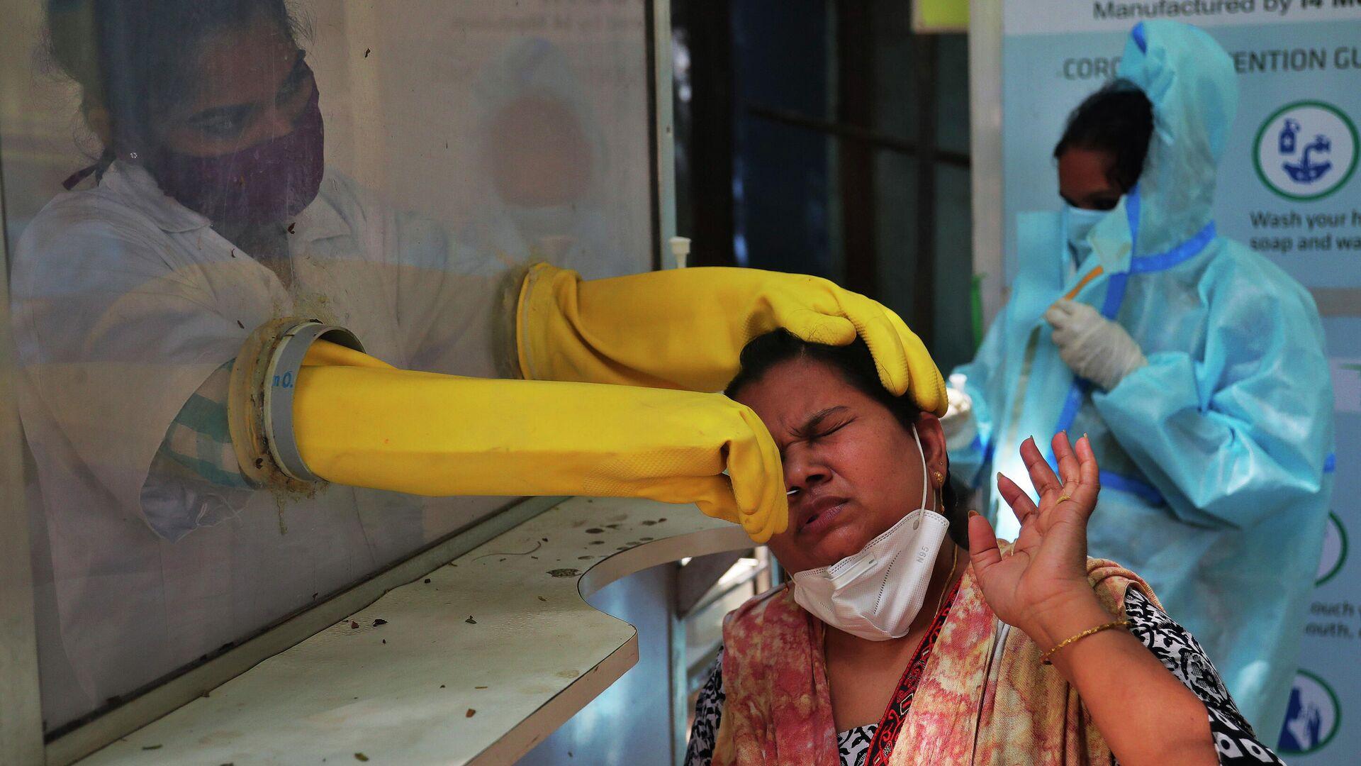 Медицинский работник берет мазок из носа для тестирования на COVID-19 в Хайдарабаде, Индия - РИА Новости, 1920, 03.01.2021