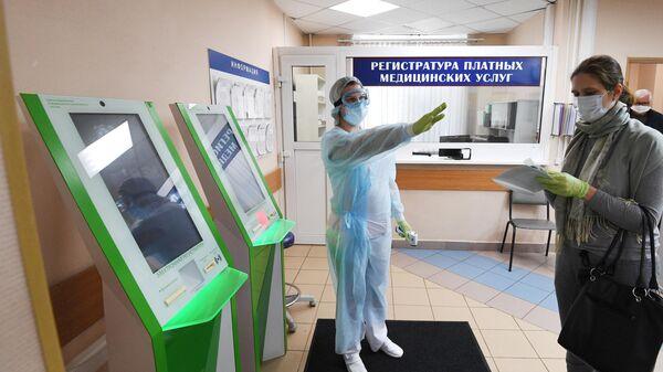 Посетитель и медработник в городской поликлинике № 209 в Москве