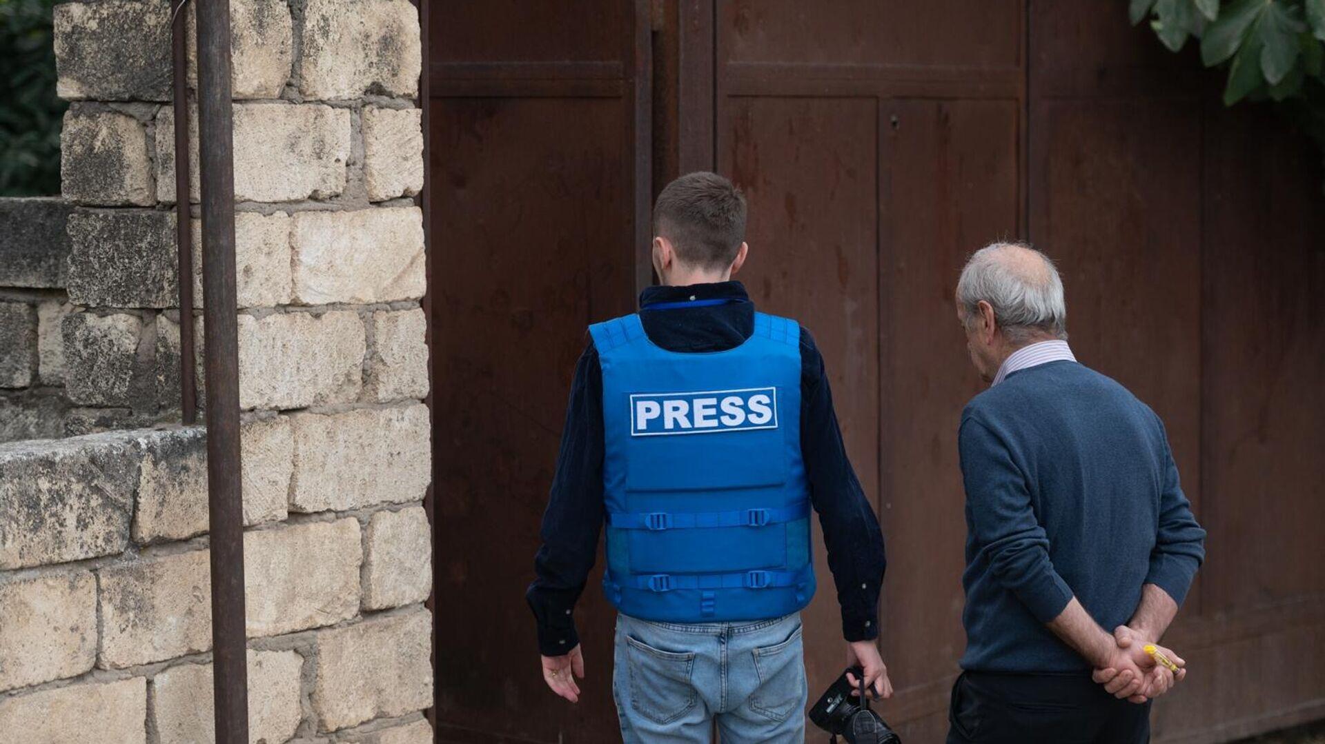 Представитель СМИ и местный житель осматривают пострадавший в результате обстрелов дом в городе Мартуни  - РИА Новости, 1920, 28.09.2020