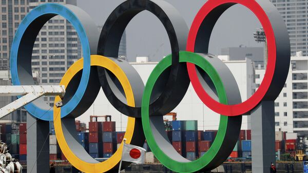 FILE PHOTO: The giant Olympic rings, which are being temporarily removed for maintenance, are seen behind Japan's national flag, amid the coronavirus disease (COVID-19) outbreak, at the waterfront area at Odaiba Marine Park in Tokyo, Japan August 6, 2020. REUTERS/Kim Kyung-Hoon/File Photo
