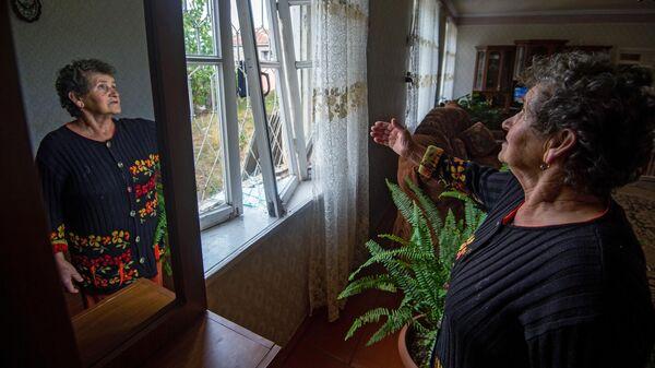 Женщина показывает выбитые окна в результате обстрелов общины Иванян Нагорного Карабаха
