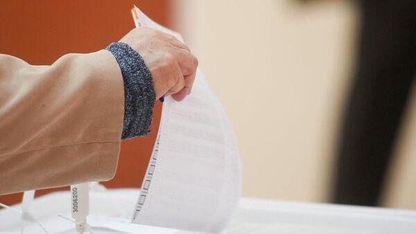 Избиратель кидает бюллетень в урну