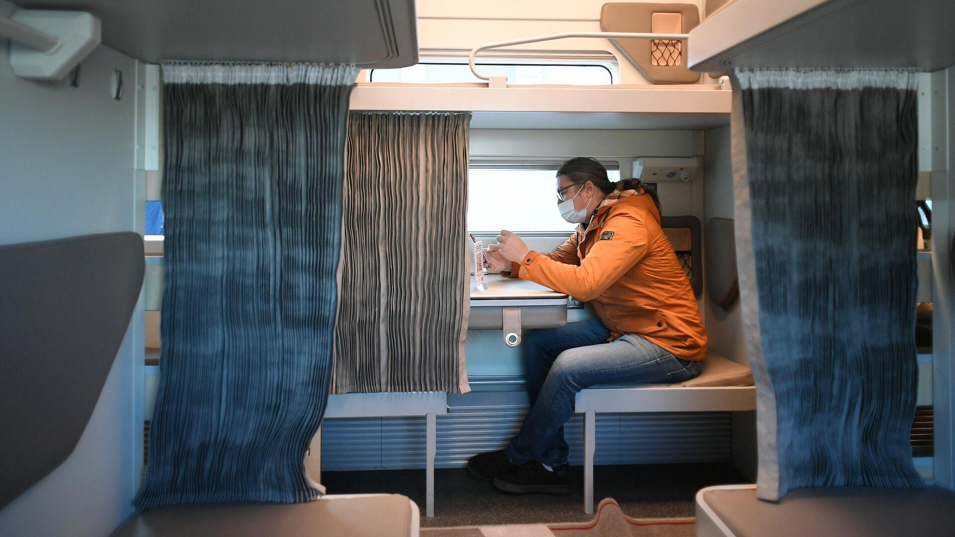 Мужчина в павильоне с макетом нового плацкартного вагона для поездов дальнего следования - РИА Новости, 1920, 22.02.2021