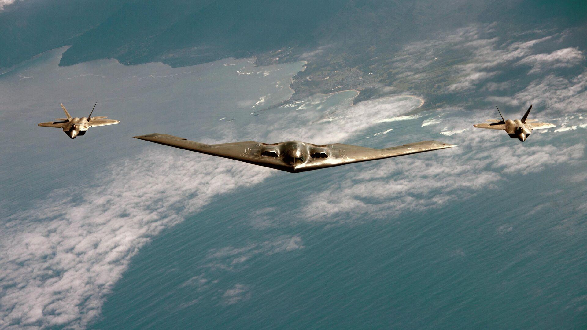 Американский малозаметный стратегический бомбардировщик Northrop B-2 Spirit в сопровождении истребителей F-22 Raptor - РИА Новости, 1920, 03.10.2020