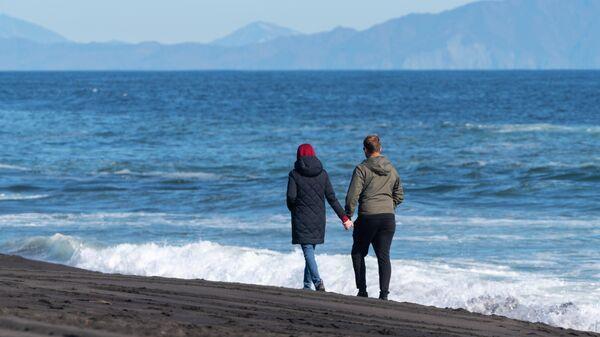 Молодые люди гуляют на Халактырском пляже Тихоокеанского побережья полуострова Камчатка