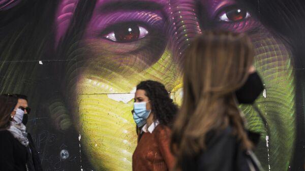 Прохожие в защитных масках на улице Гран-Виа в Мадриде