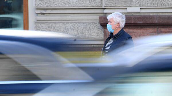 Мужчина в медицинской маске на одной из улиц в Москве