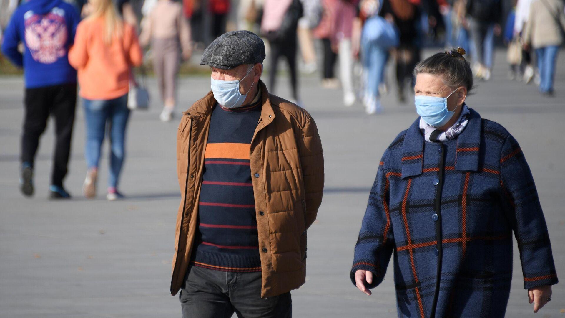 Люди в медицинских масках на территории парка ВДНХ в Москве - РИА Новости, 1920, 22.10.2020