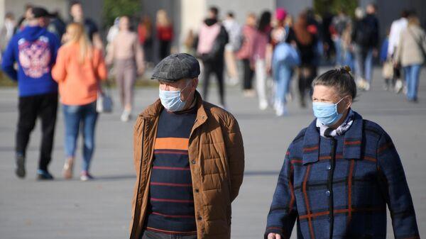 Люди в медицинских масках на территории парка ВДНХ в Москве