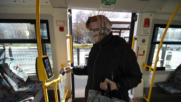 Женщина в защитной маске прикладывает социальную карту к валидатору в салоне автобуса