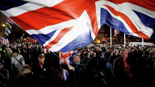 Мужчина размахивает флагом Великобритании в Лондоне
