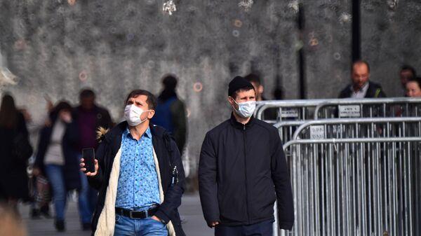 Мужчины в защитных масках на одной из улиц в центре Москвы
