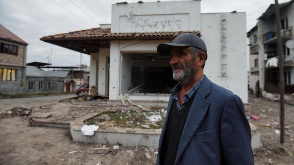 Местный житель возле дома в Степанакерте, поврежденного в результате обстрелов