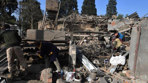Жители собирают уцелевшие вещи на развалинах своего жилого дома, разрушенного в результате ракетного обстрела города Гянджа
