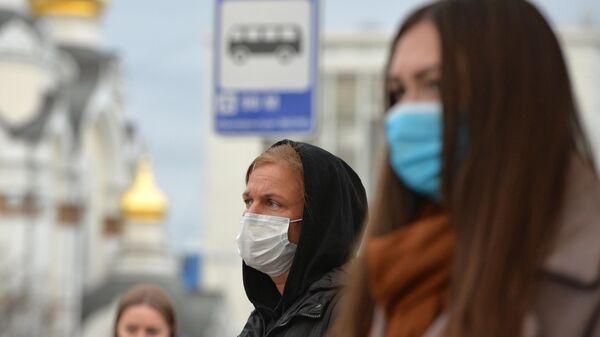 Люди в защитных масках на остановке общественного транспорта в Екатеринбурге