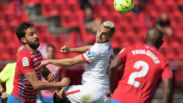 Granada's Spanish defender German Sanchez (L) and French defender Dimitri Foulquier (R) challenge Sevilla's Spanish midfielder Joan Jordan during the Spanish League football match between Granada and Sevilla at the Los Carmenes stadium in Granada on October 17, 2020. (Photo by JORGE GUERRERO / AFP)