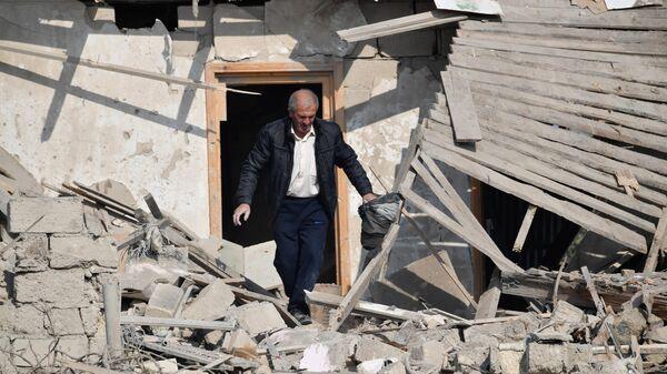 Житель Гянджи ищет свое имущество в разрушенном после обстрела доме