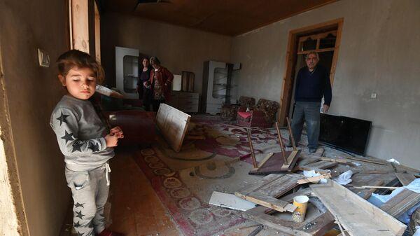 Жители Гянджи в разрушенном после обстрела доме