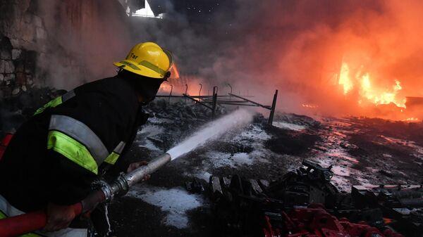 Пожарный тушит пожар на хлопковом заводе в деревне Азат Карагоинлы в Азербайджане, который возник в результате артиллерийского обстрела