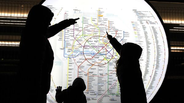 Пассажиры у схемы Московского метрополитена на станции МЦД Долгопрудная