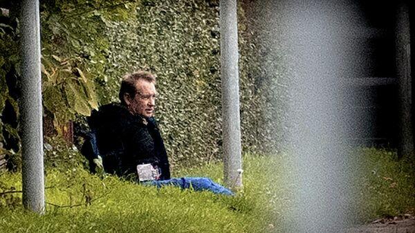 Предположительно Петер Мадсен сидит у забора в окружении полиции в Альбертслунде, Дания
