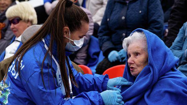 Волонтер укрывает пледом ветерана Великой Отечественной войны
