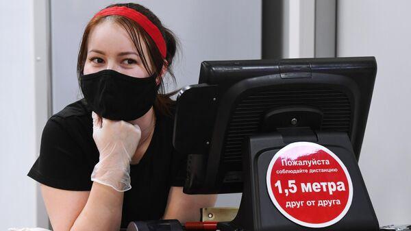 Продавец в защитной маске в одном из продовольственных магазинов Новосибирска