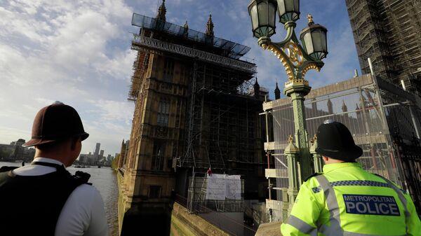 Сотрудники полиции наблюдают за протестующим в костюме человека-паука на здании Биг-Бена в Лондоне