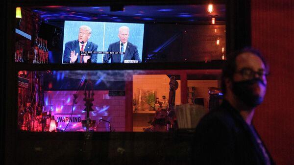 Жители Нью-Йорка смотрят трансляцию финального раунда дебатов с участием президента США Дональда Трампа и его соперника - кандидата в президенты США от Демократической партии Джо Байдена