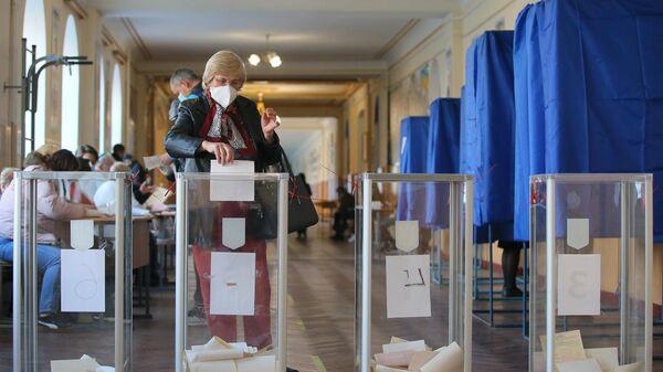Женщина голосует на одном из избирательных участков в Киеве