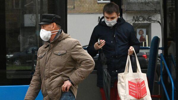 Люди в защитных масках на остановке общественного транспорта на Ленинском проспекте в Москве