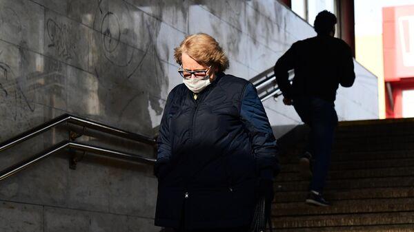 Женщина в медицинской маске в подземном переходе станции метро Марьино Московского метрополитена