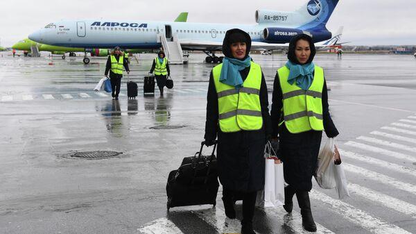 Стюардессы у самолета Ту-154 авиакомпании Алроса в аэропорту Толмачево в Новосибирске